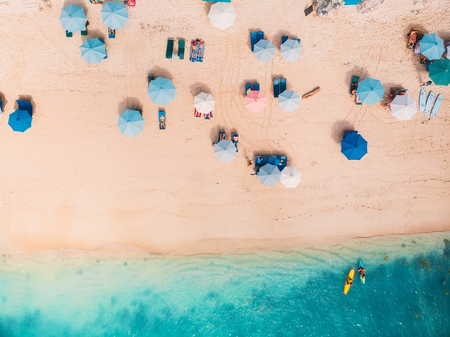 Photo pour Top view of sandy beach with turquoise sea water and colorful blue umbrellas, aerial drone shot - image libre de droit
