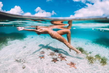 Photo pour Beautiful woman floating and relax in tropical ocean with starfish, underwater photo - image libre de droit