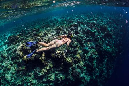 Photo pour Young woman free diver explores reef in ocean, underwater photo with diver - image libre de droit