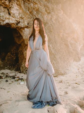 Foto de Young woman in stylish blue clothes at beach. Fashion woman. - Imagen libre de derechos