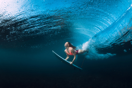 Photo pour Surfer woman dive underwater with under barrel wave. - image libre de droit