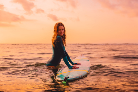 Photo pour Attractive surfer girl posing with surfboard in ocean. Surfing at sunset - image libre de droit