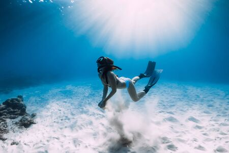 Photo for Woman freediver with fins swim over sandy bottom, underwater ocean - Royalty Free Image
