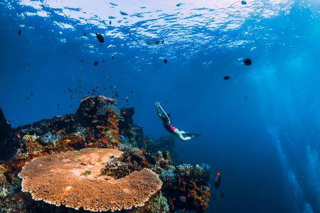Photo pour Woman freediver glides with fins at wreck ship. Freediving in blue ocean near wreck - image libre de droit