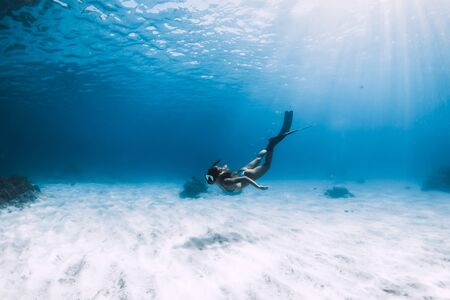 Photo for Attractive woman free diver glides with fins over sandy sea. Freediving in a tropical ocean - Royalty Free Image