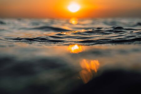Photo pour Sunset and waves in ocean. Warm water texture with bokeh - image libre de droit