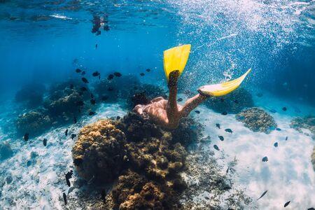 Photo pour Freediver girl with fins glides over sandy bottom in blue ocean - image libre de droit