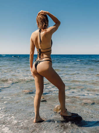 Photo pour Sexy young woman in bikini posing at stone beach. Attractive model with sporty body - image libre de droit