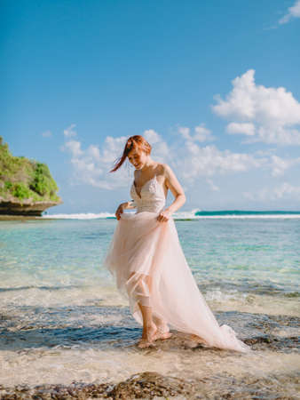 Photo pour July 5, 2020. Bali, Indonesia. Wedding day of red head bride in wedding dress at tropical beach. Happy wedding in tropical Bali - image libre de droit