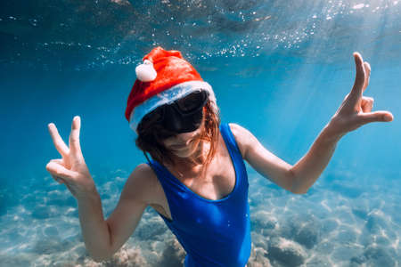 Photo pour Happy freediver woman with New year cap glides underwater in blue ocean. Christmas holidays concept - image libre de droit