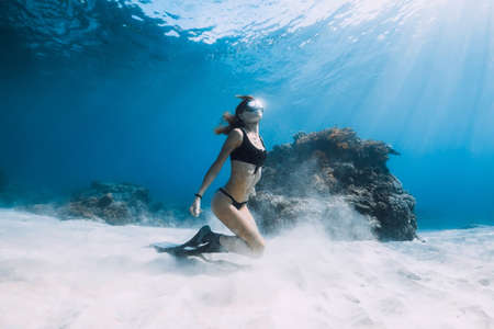 Photo pour Freediving underwater in blue ocean. Sporty woman freediver swim with fins and corals. - image libre de droit