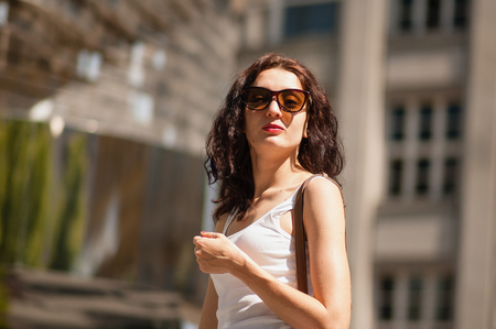 Curly brunette in sunglasses. Arrogant and confident look. Portrait, Prague, May 28, 2017, near the monument to Hlava Franze Kafka.