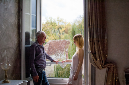 Foto de Portrait of Couple with Age Difference Standing near Opened Window inside the House During Summer Sunny Day. - Imagen libre de derechos