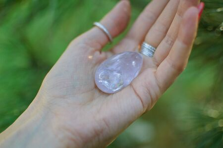 Photo for Female hand with transparent amethyst quartz yoni egg for vumfit, imbuilding or meditation. Shining crystal egg in hands on sky and sunrise background outdoors. Womens health concept. - Royalty Free Image