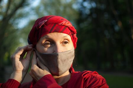 Photo pour Mature woman wearing handmade textile face mask as accessory and protective element during sunny spring day in the park because of coronavirus pandemic - image libre de droit