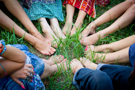 Bare feet of group of young girls in a circle on a green grass