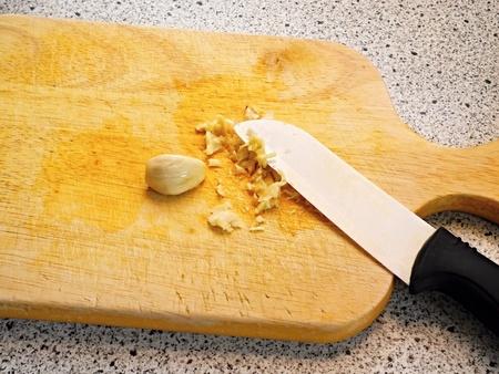 Rubbing fresh garlic on wooden chopping board ceramic knife.