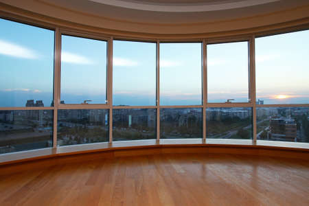 Big glass wall in oval living room with view