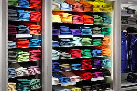 Various colour shirts at shelf in shop
