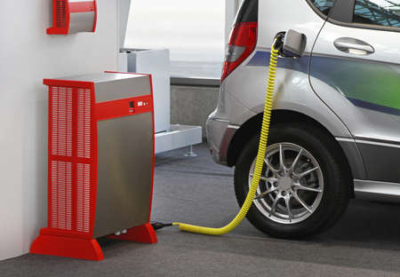 Electric vehicle with plugged cable in charging station