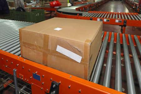 Foto für Shipping Box at Conveyor Belt in Distribution Warehouse - Lizenzfreies Bild