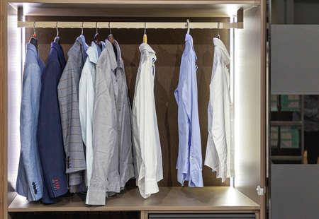 Photo pour Business Shirts and Suits at Hangers in Wardrobe Closet - image libre de droit