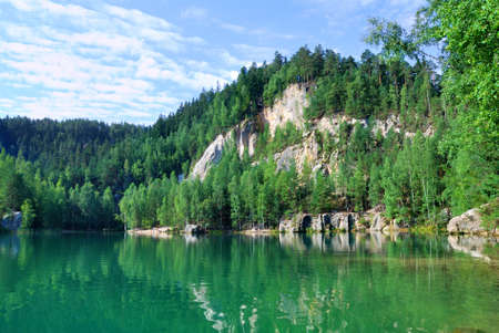 Green water lake and rocky bank with lush trees