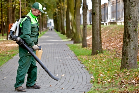 Photo for Landscaper operating gasoline Leaf Blower while cleaning the tracks in the park - Royalty Free Image