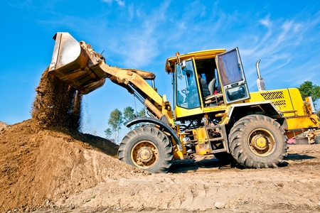 Photo for Wheel loader machine unloading soil during earthmoving works at construction site - Royalty Free Image