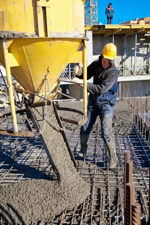 Construction worker pouring concrete during commercial concreting floors and building reinforced concrete structures