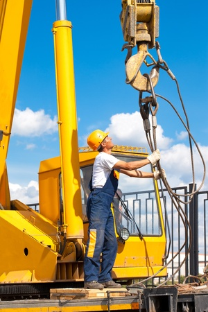 Construction worker in uniform and protective gear during hoisting works by mobile crane