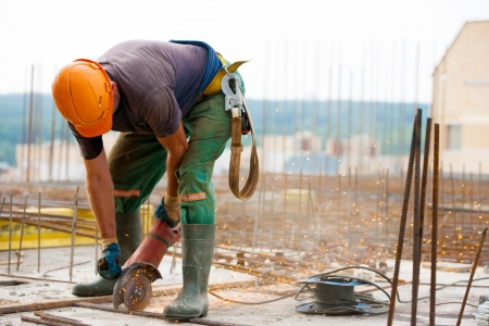 Industrial worker cutting metal rebar at construction site w