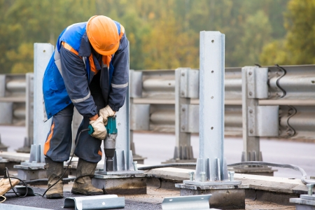 Laborer worker tightening bolts with Electric Impact Wrench tool during construction road works on installation traffic barrier