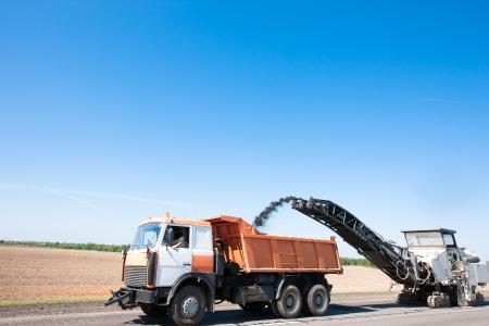 Milling machine loading crushing Asphalt into Dump Truck during repairing road works