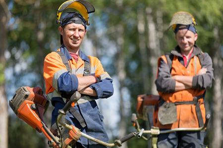 Foto de Happy professional garden workers with petrol string trimmers outdoors - Imagen libre de derechos