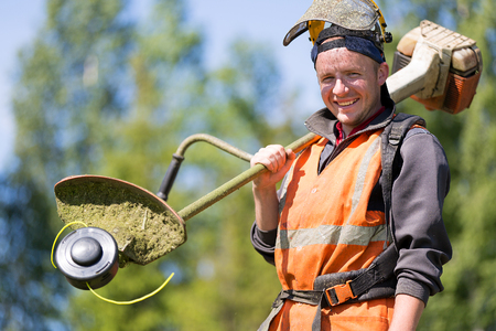Portrait happy gardener or road landscaper man worker with gas grass trimmer equipment