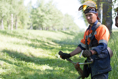 Photo for Portrait landscaper man worker during grass cutting with gas handheld string trimmer equipment - Royalty Free Image