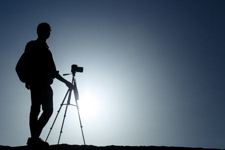 Photo for A photographer with tripod with sun and blue sky - Royalty Free Image