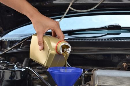 Car servicing mechanic pouring oil to engine