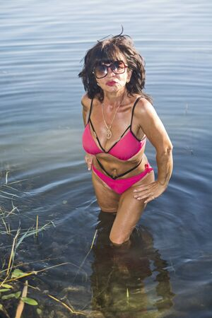 Photo pour A middle-aged beautiful and tanned lady in a bikini comes out of the water and poses. - image libre de droit