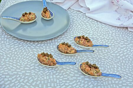 Specialty salmon meat with spices on the table. The meat is decoratively presented in ceramic spoons.