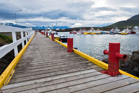 Colorful pier for fishing boats at Dalvik harbor in north Iceland
