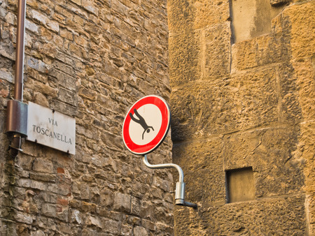 Funny artistic modification of a traffic sign in a small alley at downtown of Florence in Tuscany, Italy