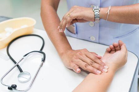 Nurse is measurement radial pulse at the wrist of the patient.