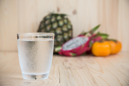 Drinking water and persimmon, dragon fruit, pineapple on wooden background