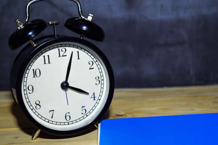 Concept vintage background black retro alarm clock on 16.00 pm or 04.00 am and blue book