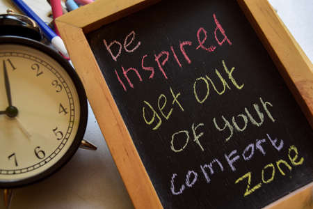 Photo for be inspired get out of your comfort zone on phrase colorful handwritten on chalkboard, alarm clock with motivation and education concepts - Royalty Free Image
