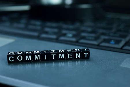 Photo pour Commitment text wooden blocks in laptop background. Business and technology concept - image libre de droit