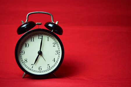Clock ticking to 7 o'clock on the red background