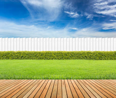 Photo for Lawn and wooden floor with hedge and White fence on blue sky background - Royalty Free Image
